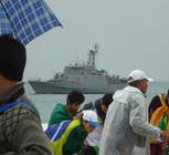 A battleship keeps watch from the water as pilgrims await Pope Francis' arrival.