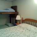 Bedroom with one queen bed and two twin bunks.