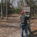 A hiker checking out a trail junction map.