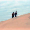 Hikers climbing a dune at Silver Lake State Park.